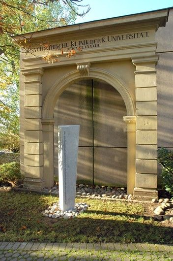 Entrance gate of the first clinic building from 1893 with the stele erected in 2014 in memory of the victims of National Socialism. (Design: Tilmann Christner, Execution: Steinwelten by Josef Hofmann)